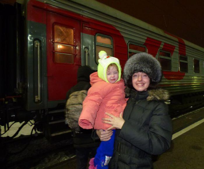 Jeune femme russe portant enfant et chapka sur le quai d'une gare du Transsibérien. Photo : Nord Espaces